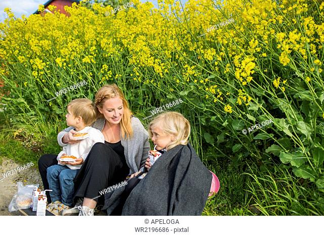 Smiling woman sitting with children having snacks at oilseed rape field