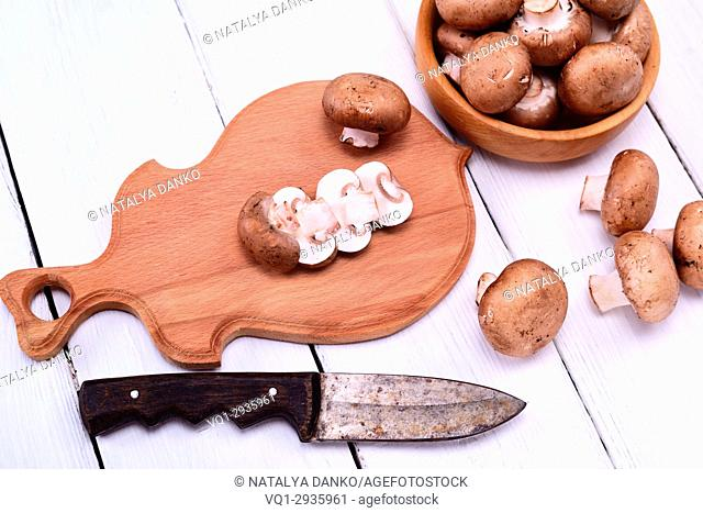 chopped fresh mushrooms champignons on a brown wooden cutting board
