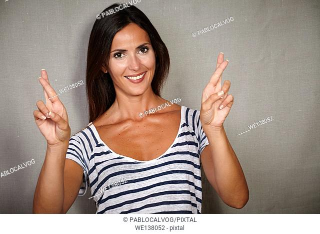 Good-looking woman crossing fingers while expecting against grey texture background