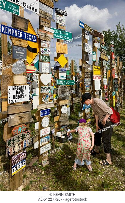 Mother and daughter explore the Signpost Forest, Watson Lake, Yukon Territory, Canada, summer