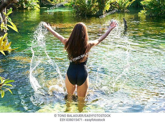 Beautiful teen girl in cenote of Riviera Maya splashing water with swimsuit