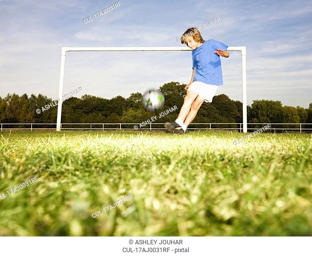 Boy kicking football in front of goal