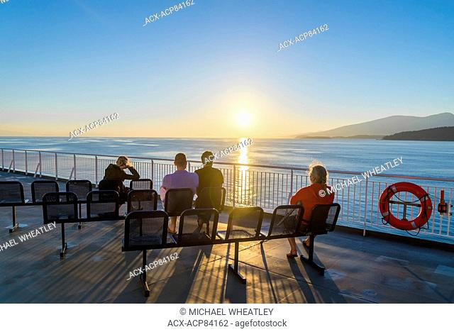 Passengers enjoy sunset from deck of BC Ferry, British Columbia, Canada