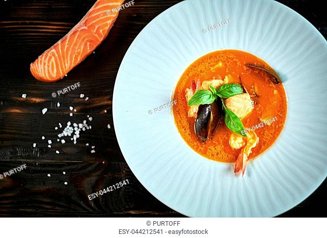 Homemade seafood soup with tomato sauce and coconut milk on an old wood tray jpg