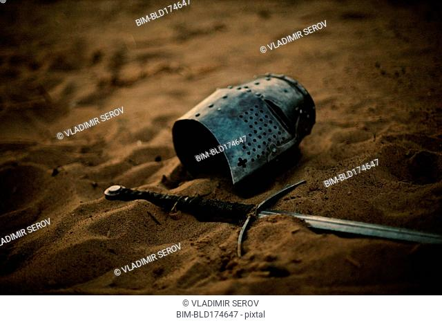Medieval helmet and sword in sand