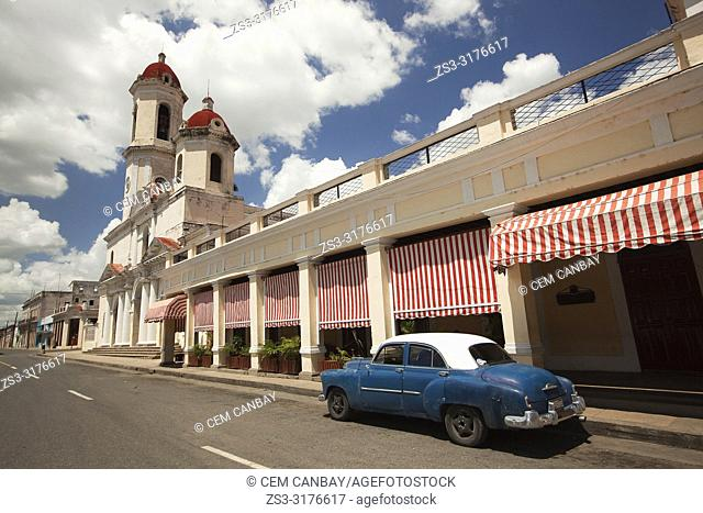 Old American car parked at the rstreet side in front of the Purisima Concepcion Cathedral in Jose Marti Park, Cienfuegos, Cuba, Central America
