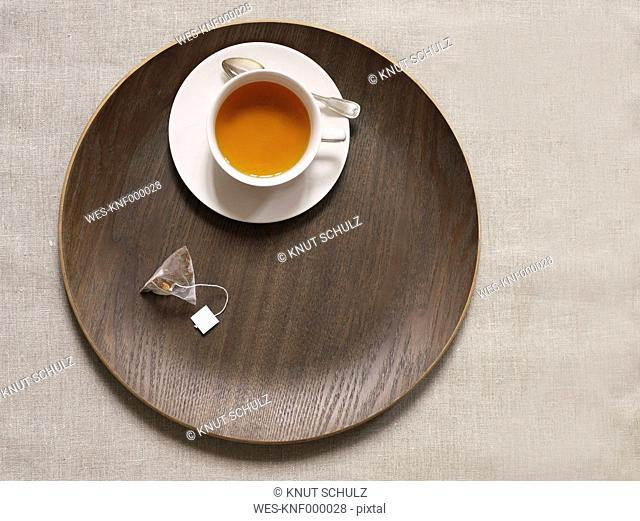 Tea cup on wood tray with tea bag