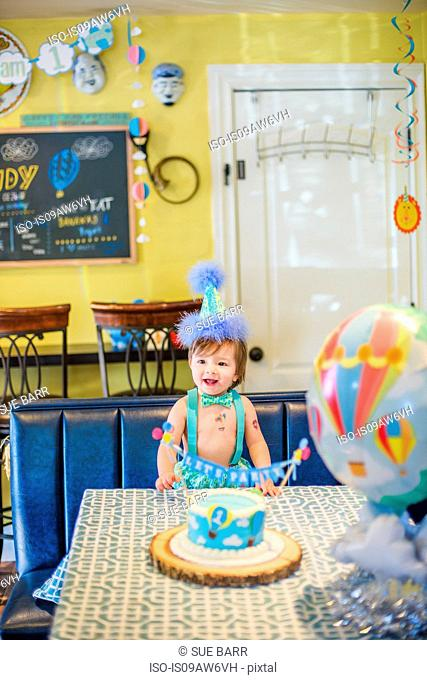 Baby boy wearing party hat with first birthday cake at table