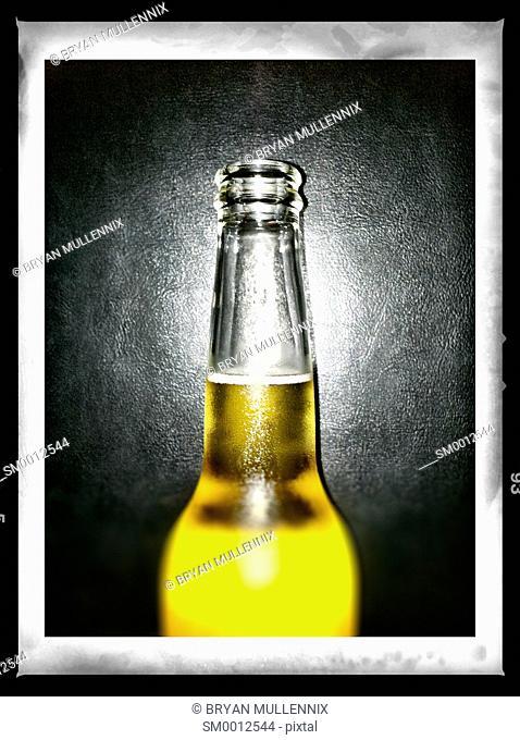 A cold beer bottle against a black backdrop (mobile image)