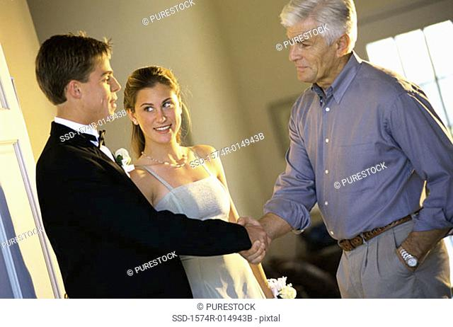 Close-up of a father shaking hands with his daughter's date