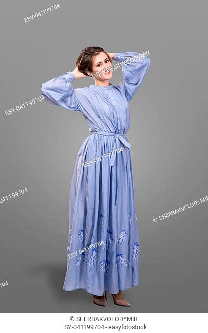 Smyling femail model wear long blue dress isolated over gray background