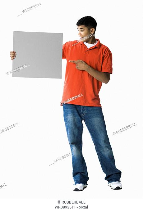 Young man pointing towards a blank sign