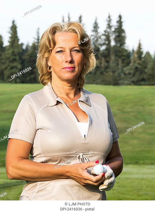 Portrait of a female golfer on a golf course; Edmonton, Alberta, Canada