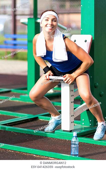 Sport Concepts.Happy Flirting Caucasian Female Athlete in Having Her Rest Time During Training On Belly Workout Tool Outdoors.Vertical Image