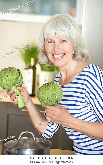 Elderly woman cooking artichoke