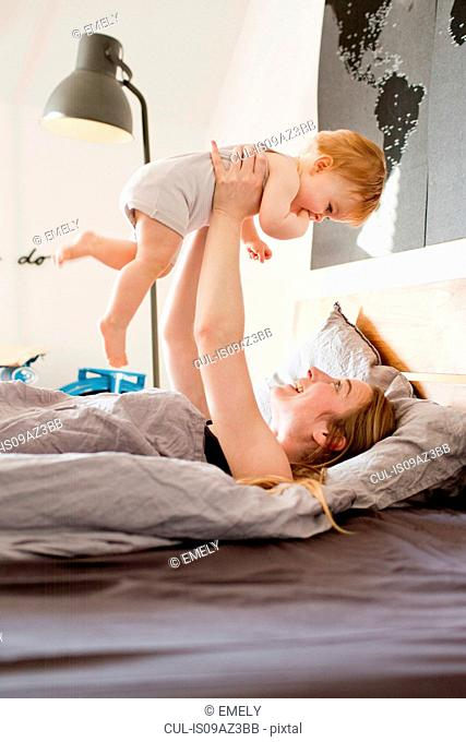 Mid adult woman holding up baby daughter in bed