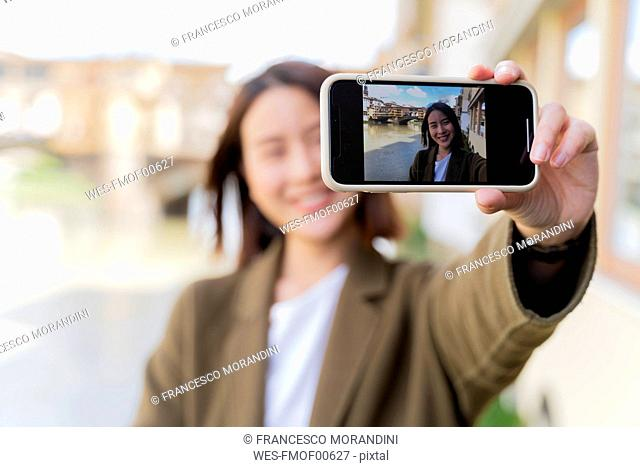 Italy, Florence, young tourist woman taking a selfie at Ponte Vecchio