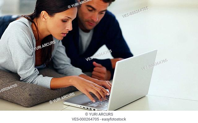 Attractive young couple lying on the floor using a laptop together