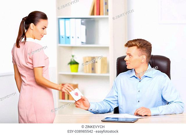 Secret note. Young appealing woman stops at the desk to pass a love note to her romantic partner
