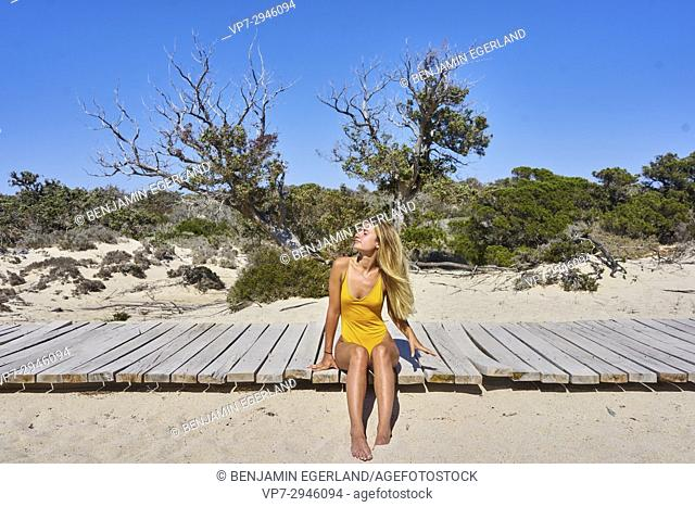 beautiful young woman sitting in swimsuit in the sand. Dutch ethnicity. At holiday destination Chrissi Island, Crete, Greece
