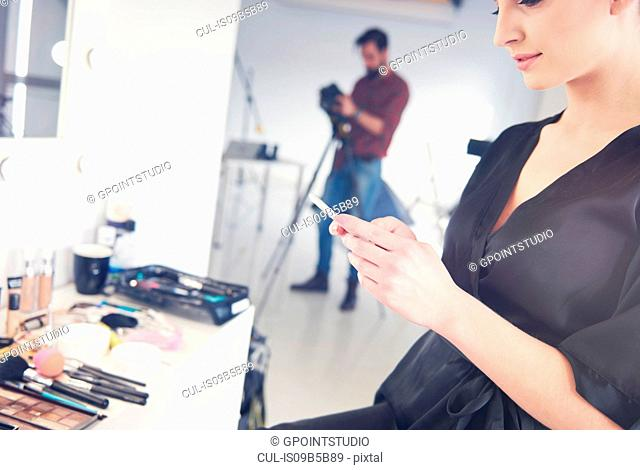 Young female model looking at smartphone before photo shoot