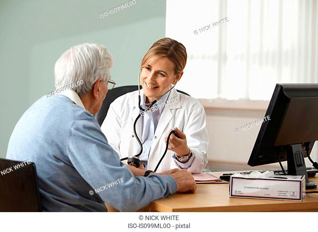 Doctor taking senior mans blood pressure