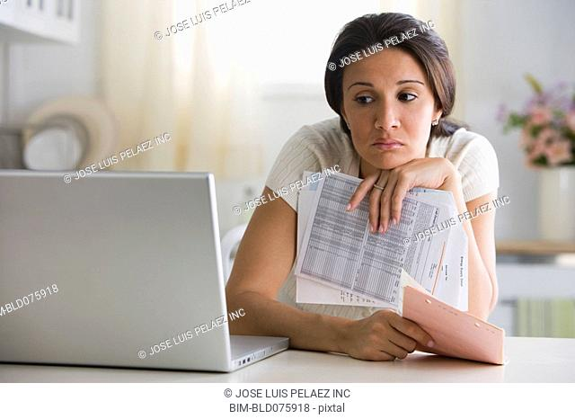 Worried woman holding bills and looking at laptop