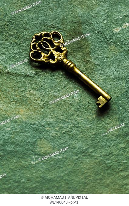 Brass skeleton key abandoned on the ground