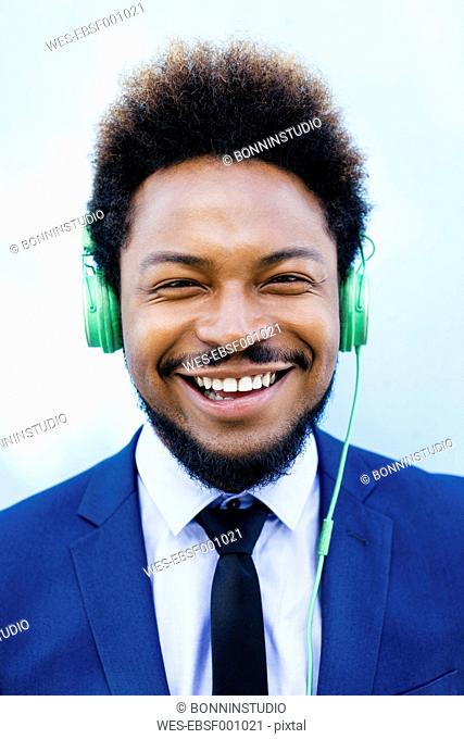 Portrait of smiling young businessman hearing music with headphones