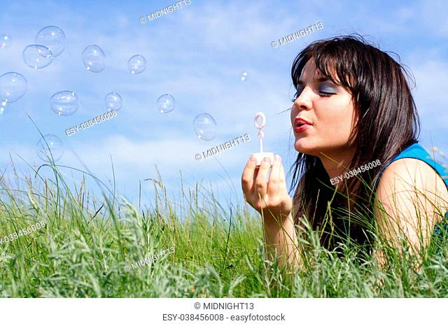 young girl starts up soap bubbles on a background of the blue sky