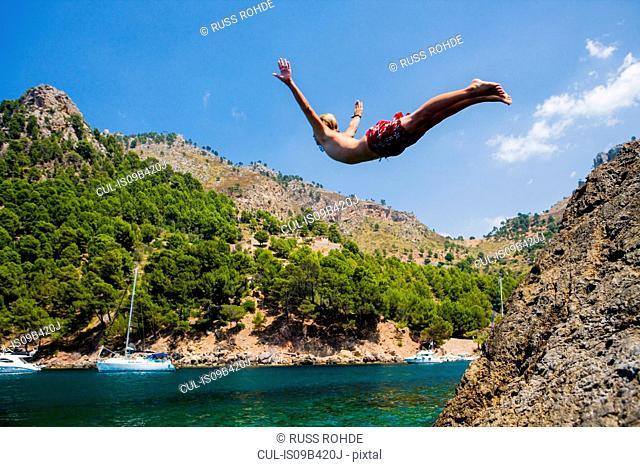 Young man diving into sea, Cala Tuent, Majorca, Spain