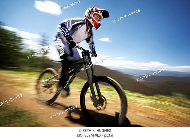 Female mountain biker speeding down dirt track