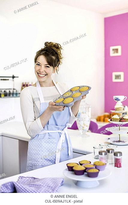 Woman holding up tray of homemade cupcakes