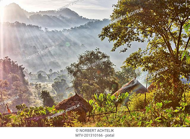 Thatched hut with silhouetted mountains in background during sunrise
