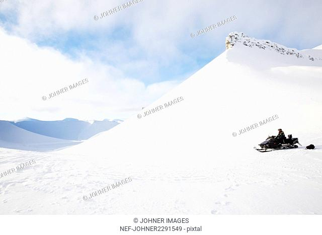 Man on snowmobile in winter landscape