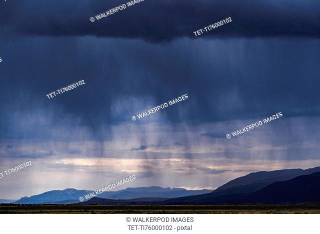 Storm clouds with rain over mountains