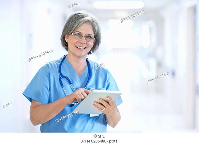Mature female doctor using tablet