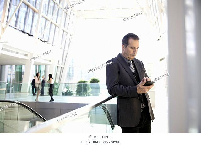 Businessman texting with cell phone in atrium