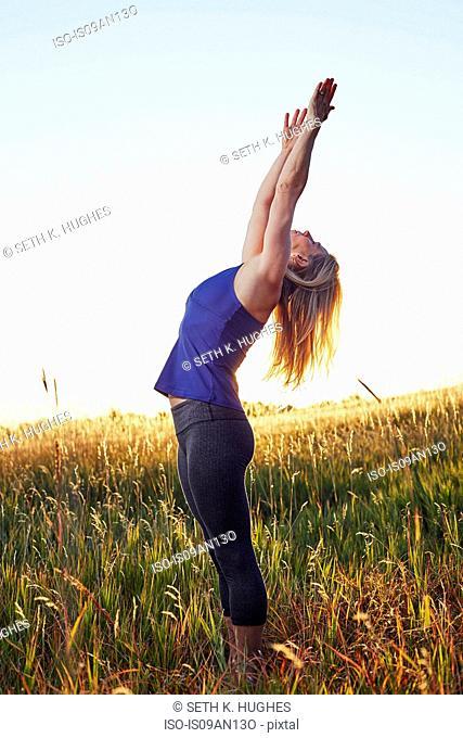Mature woman practising yoga on field