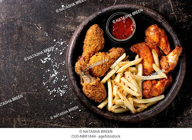 Fast food fried crispy and spicy chicken legs, wings and french fries potatoes with salt and ketchup sauce served in stone plate over dark texture background