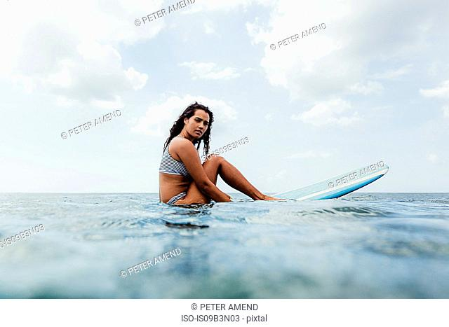 Surface level view of woman on surfboard looking at camera, Oahu, Hawaii, USA