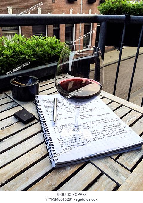 Tuinstraat, Tilburg, Netherlands. Analog notebook and pen, with a glass of red wine on top of a balcony table