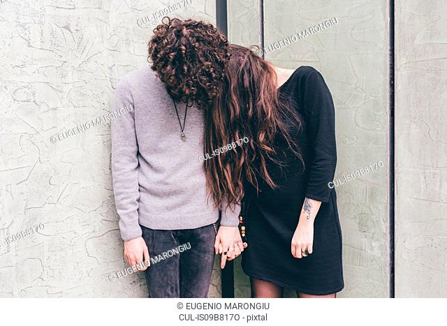 Young couple outdoors, standing against wall, holding hands, hair covering their faces