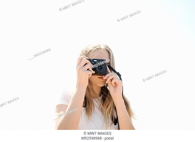 Teenage girl with long blond hair looking through a camera, taking a picture