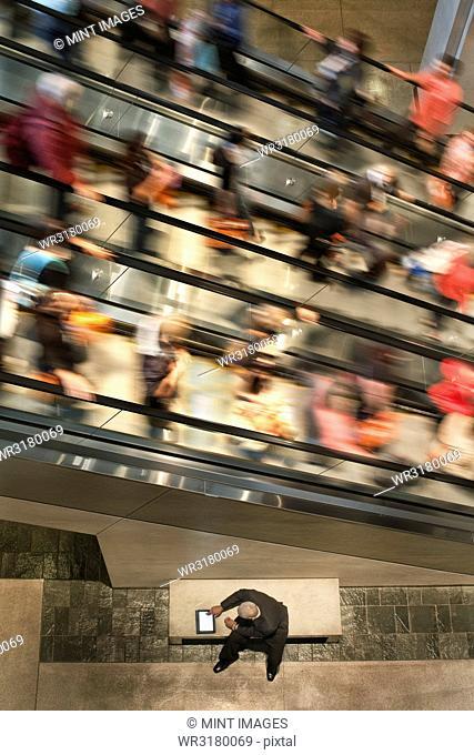 Businessman on a notebook computer near an escalator full of people