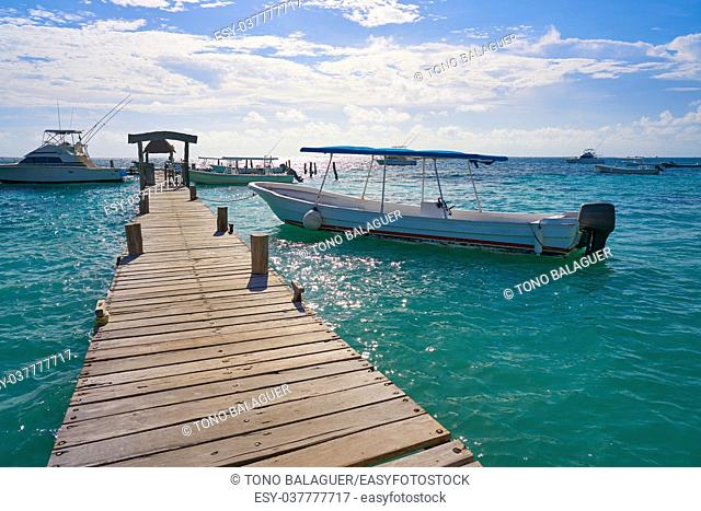 Riviera Maya wood pier with Caribbean boats in Mexico