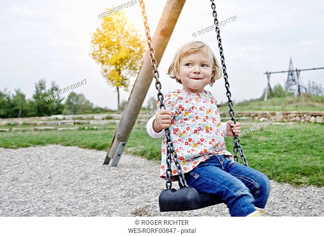 Smiling girl on swing on playground