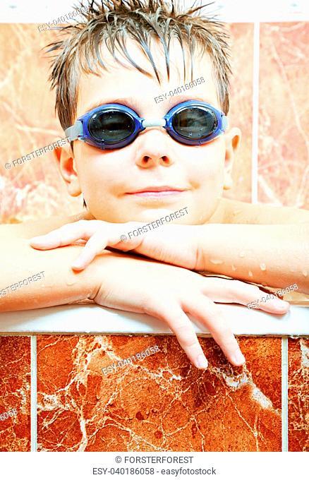 Cute boy in blue swimming goggles leaning on bath edge