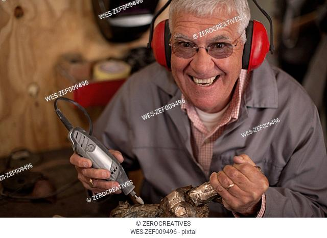 Happy senior man working on bronze cast