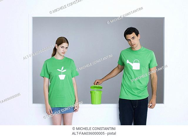Young adults wearing tee-shirts printed with watering can and potted plant, man opening small garbage can